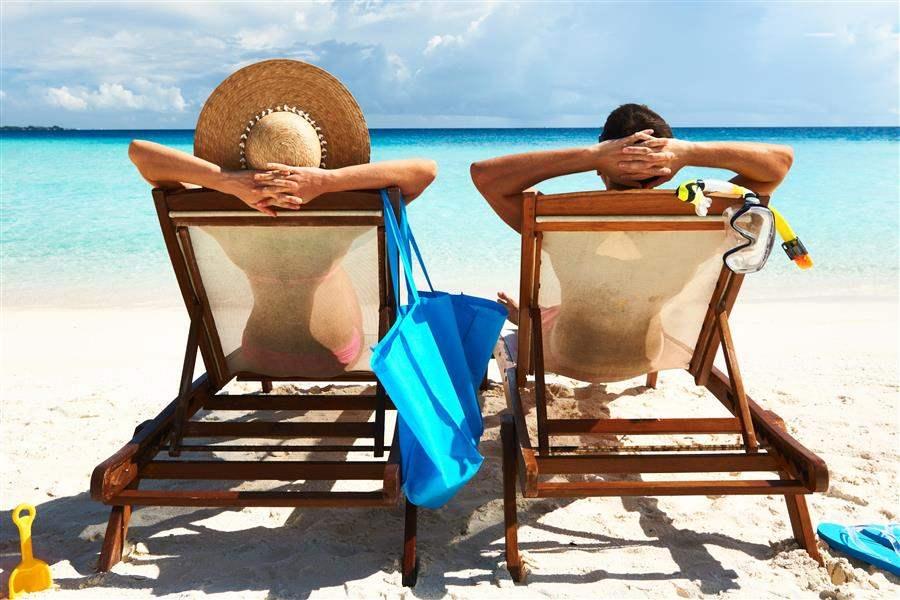 Sunloungers on white tropical beach