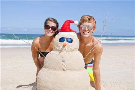 Couple on beach with sand snowman