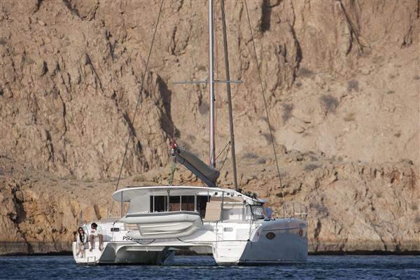 Catamaran by cliffs